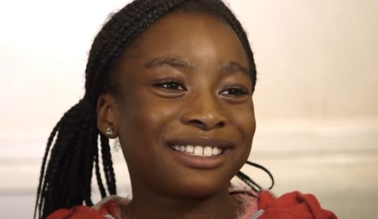 A young girl with plaited hair smiles as she recounts a story to the camera