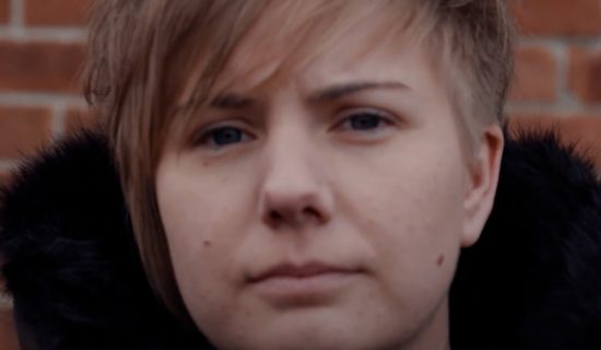 Close up on the face of a young woman. She is looking directly into the camera, with a neutral face. She is standing in front of a brick wall.