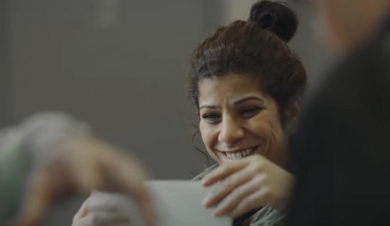 A woman is smiling as she holds and reads a piece of paper. She is in a room with other people around her.