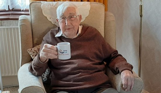 Charlie at Age UK Ealing, an elderly man seated in an armchair holding an Age UK mug