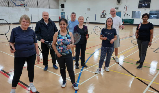 Adults stand and smile while holding badminton rackets in a sports hall