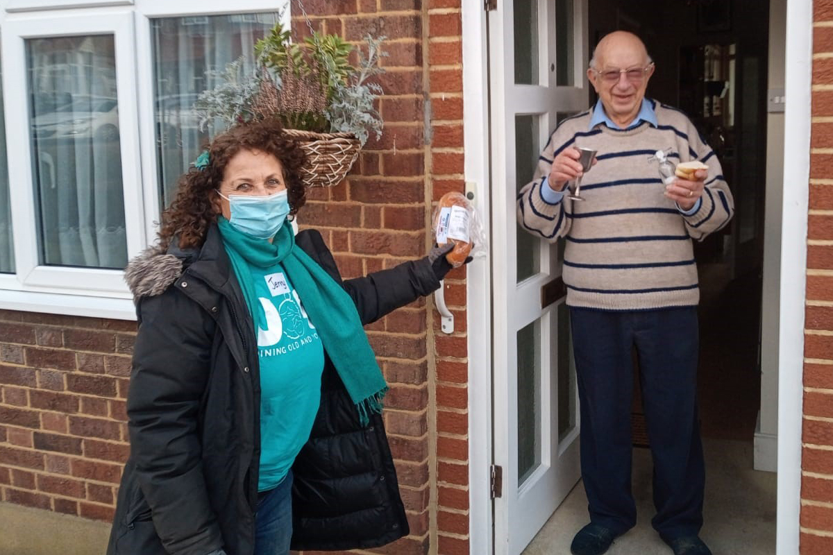 A volunteer from JOY makes a regular weekly visit to an elderly Jewish gentleman, who smiles from his front door. The project is run with Jewish Care's Holocaust Survivor's Centre