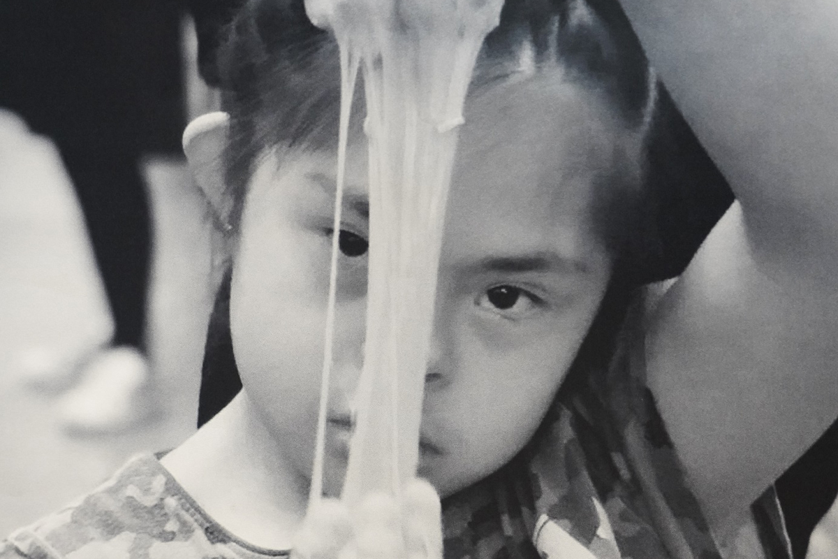Esmeralda, an autistic child, looks towards the camera while stretching gooey play-stuff between her hands
