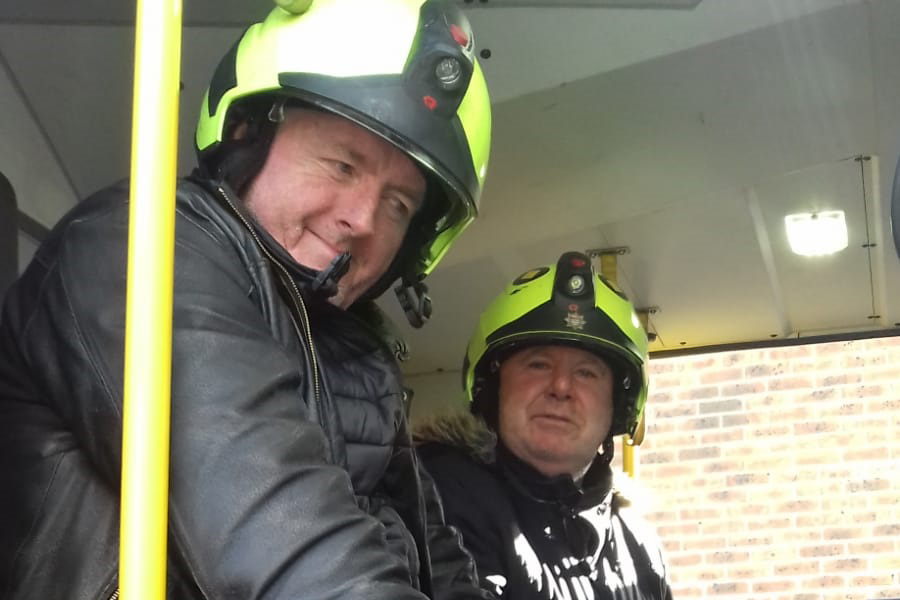 Two middle-aged men sit together, wearing fire-fighters' helmets, inside a fire engine.