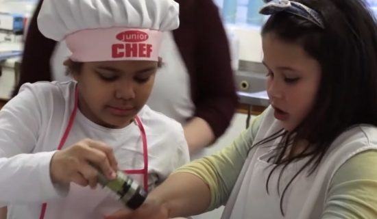 Two young girls are preparing food in a kitchen, while others also work around them. One of the girls is wearing a hat which says 'Chef'