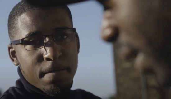 Close up on two young black men's faces as they talk outdoors