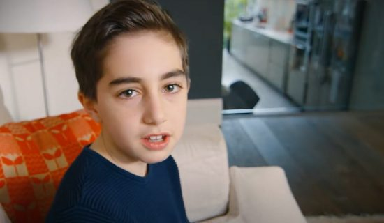 A young boy is sitting on a sofa and looking up at the camera. He appears to be speaking.
