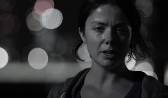Black and white image of a young woman looking into the screen. She is outside, at night, with blurred street lights in the background. LandAid video clip