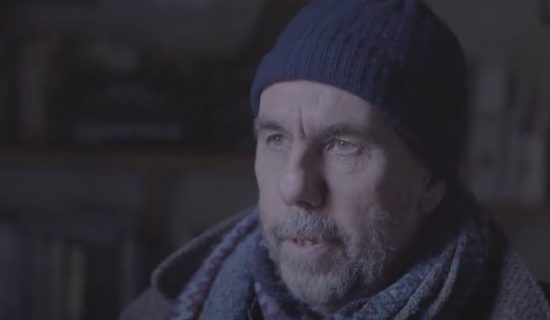 A middle-aged man in winter clothing, including a hat and scarf, is talking to someone off-screen. He is outdoors in a dark setting.