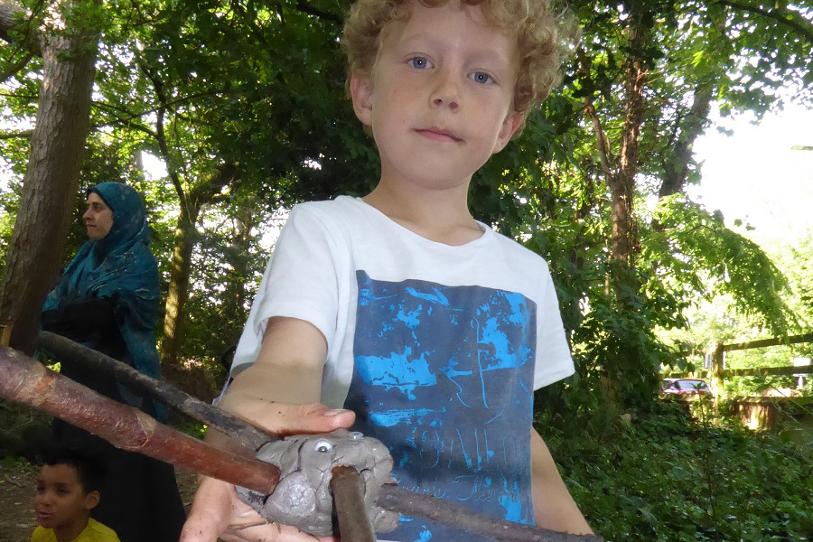 A young boy in a t-shirt shows off an 'animal' made with a clay body and sticks for legs.