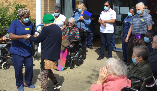 Elderly patients and carers dance outside a care home