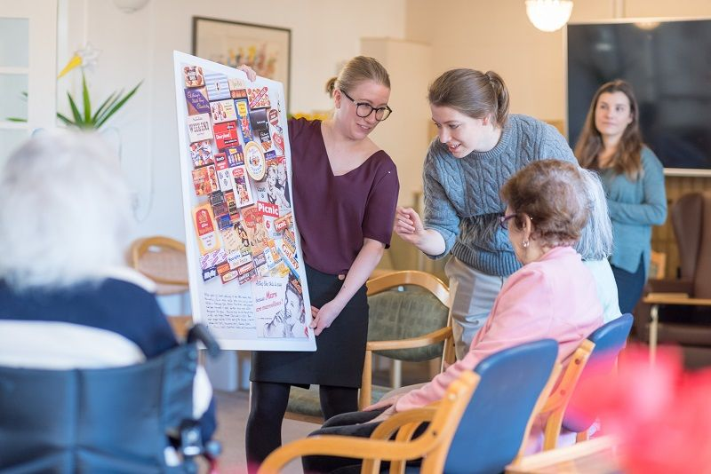 Erin Tuckey and Alina Tiits from the Museum of Brands running a reminiscing session at Victoria Care Centre, in Park Royal. They are holding up a poster showing lots of old brand labels, to trigger memories.