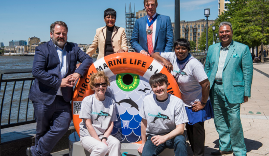 The Lord Mayor stands with others around a new bin, installed by the marine conservation charity GreenSeas Trust besides the Thames