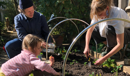 A child and two adults prepare a vegetable bed