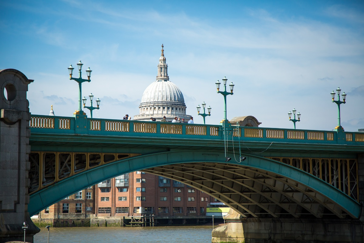 Southwark Bridge, with the dome of St Pauls rising behind it, under a blue sky