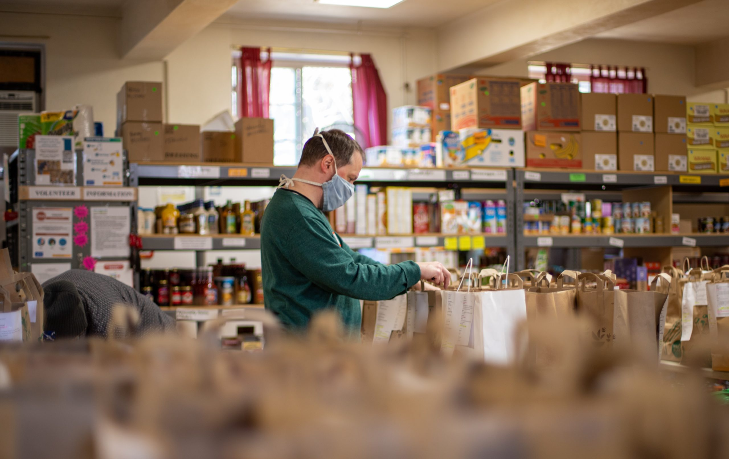 A man sorting bags of groceries in a food bank. Photo by Aaron Doucett.
