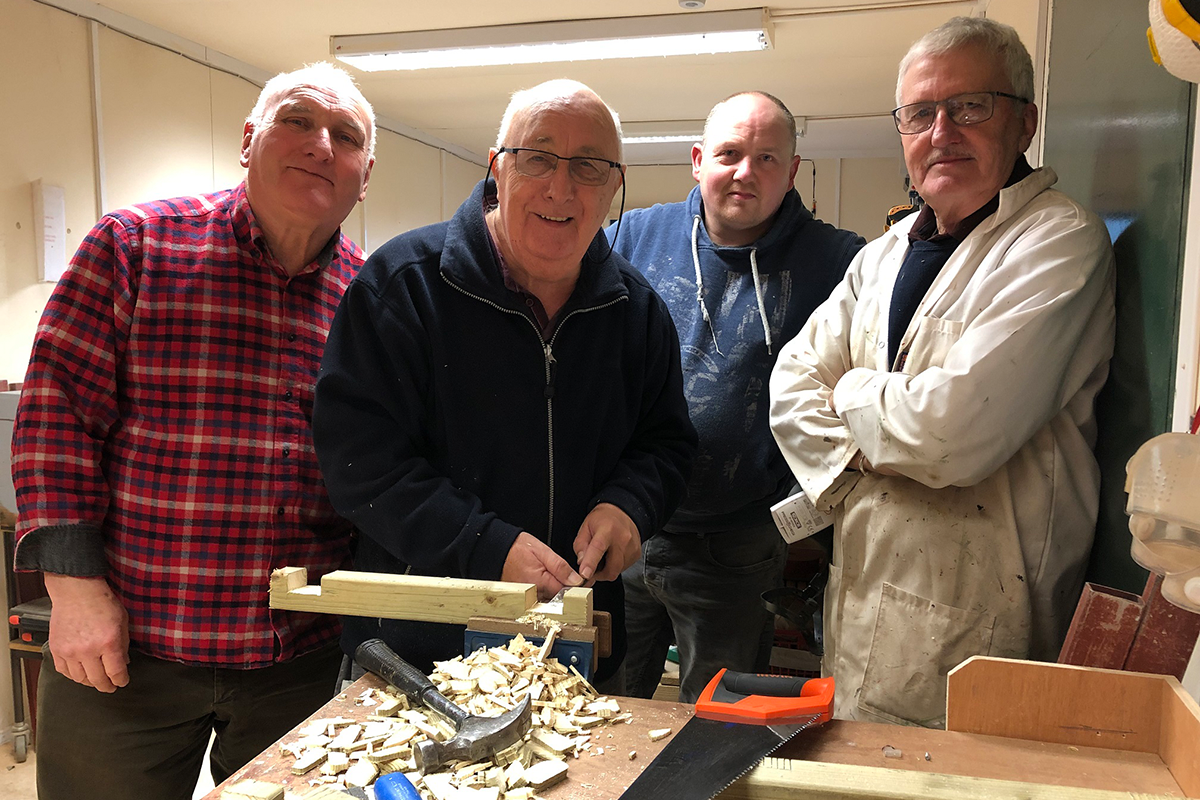 Four men in a modern shed, smiling and standing at a table covered with wood shavings from wood-working.