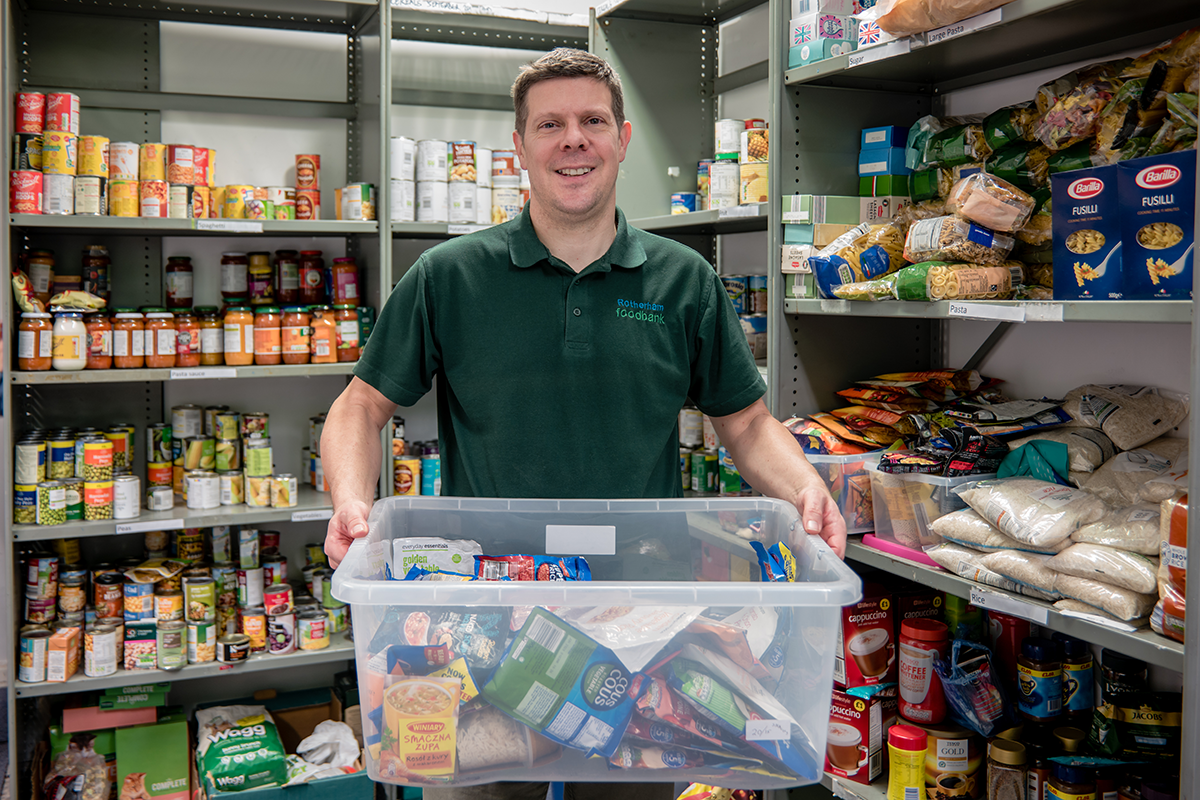 A smiling man, holding a box of packaged foods, in a food bank, where donated food is placed all around on shelves.