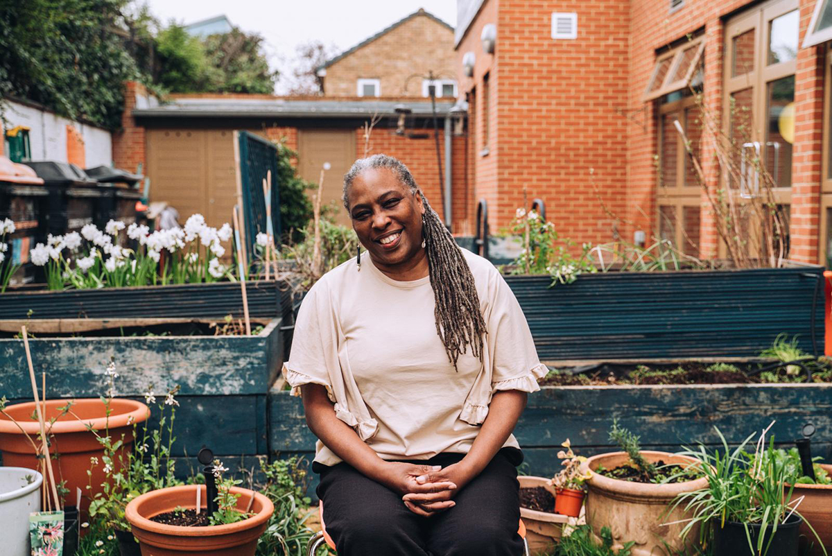 A smiling woman sits in an urban community garden, surrounded by pots and planters
