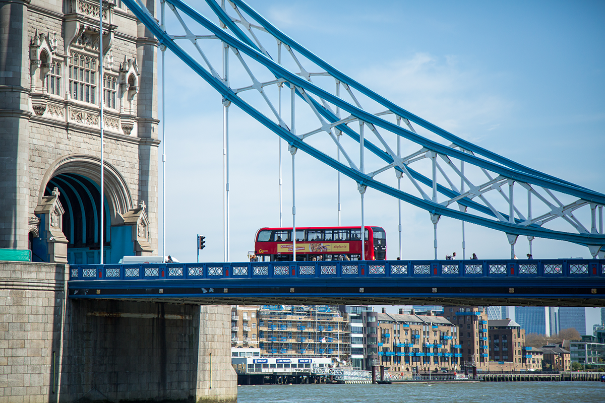 A photograph of Tower Bridge, showing a red bus against a blue sky.