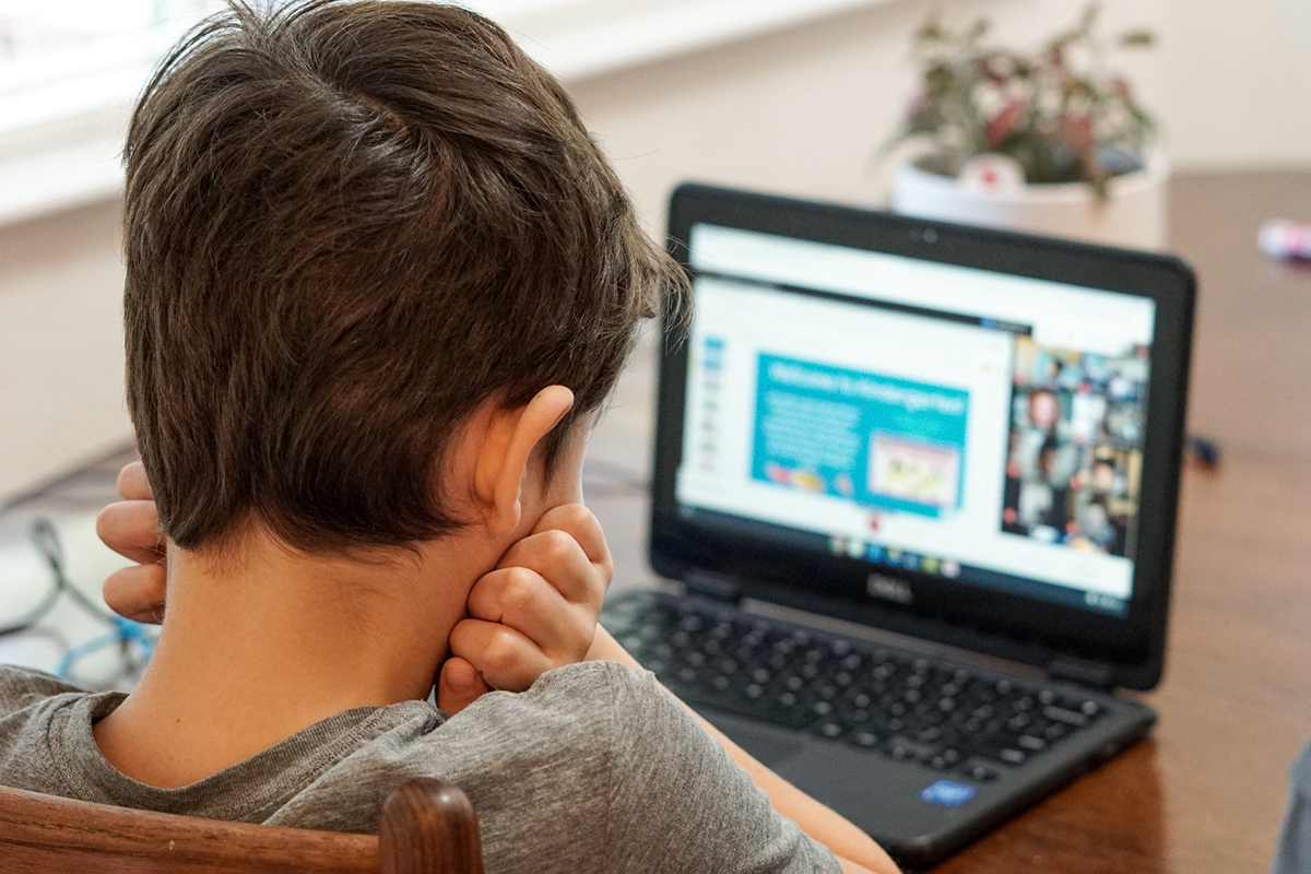 Child looking at laptop, with head in hands